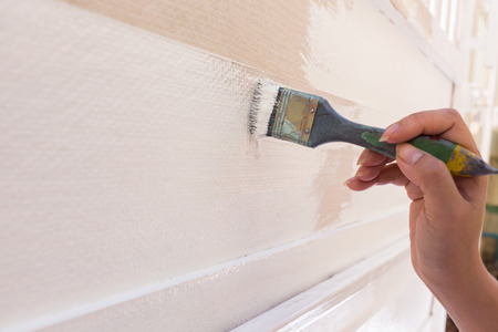 pintor de casas: blanco en la cerca de madera trabajador mano que sostiene la pintura del cepillo