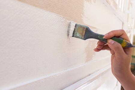 peintre en b�timent: travailleur de main tenant la peinture au pinceau blanc sur une cl�ture en bois Banque d'images