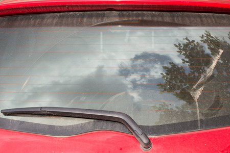 windshield wiper on dirty back glass of car photo