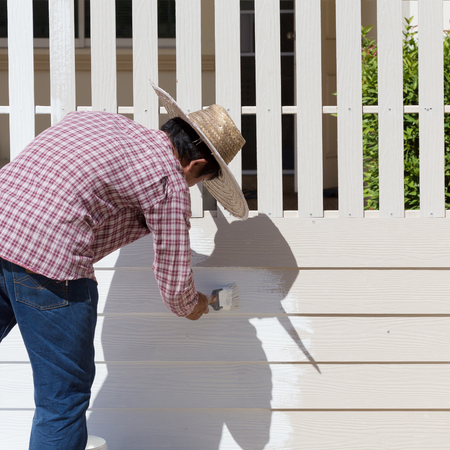 fence panel: worker painted white fence with brush Stock Photo