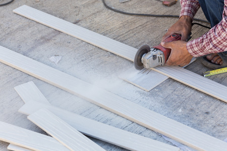 carpenter hands using electric saw on wood at construction site photo