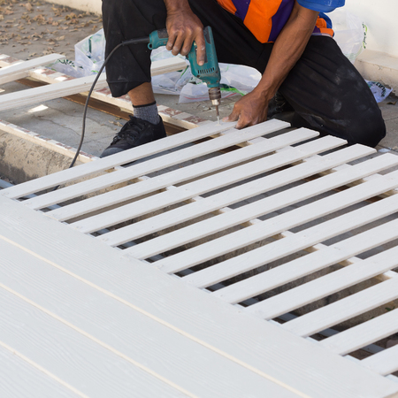 carpenter hands using electric drill on wood at construction site 写真素材