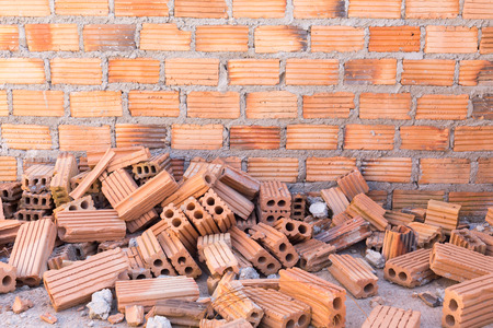 pile of bricks in construction site with brick wall background photo