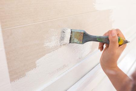 de hand werknemer met penseel schilderen wit op houten hek Stockfoto