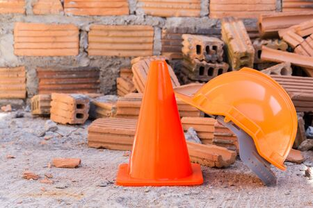 industrial accident: construction helmet safety and cone in construction site with bricks Stock Photo