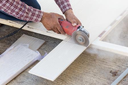carpintero: manos Carpintero que usa la sierra eléctrica en la madera en el sitio de construcción