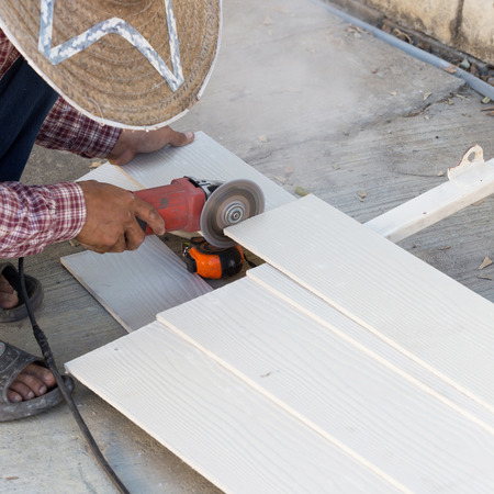 electric saw: carpenter hands using electric saw on wood at construction site