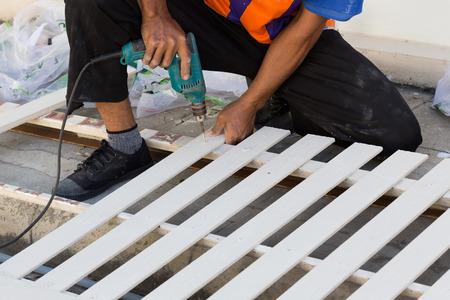 timmerman handen met behulp van elektrische boor op hout op de bouwplaats