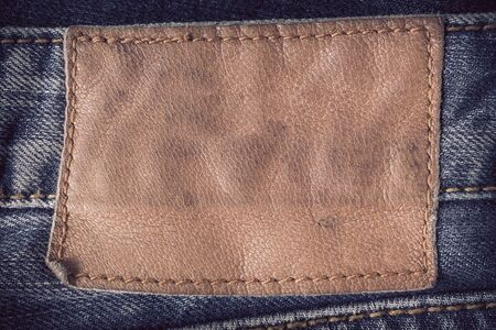 sew tags: brown leather tag on blue jeans Stock Photo