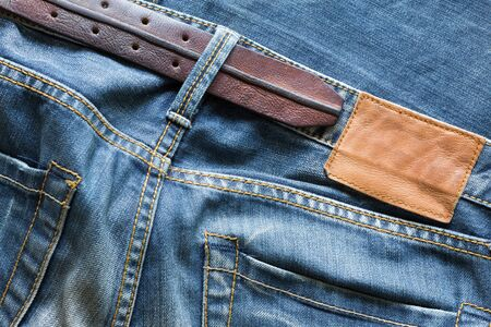 sew tags: blue jeans with leather belt and label tag