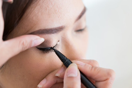 eye liner: makeup beauty with brush eye liner on pretty woman face