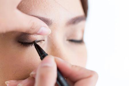make-up schoonheid met borstel eyeliner op mooie vrouw gezicht Stockfoto
