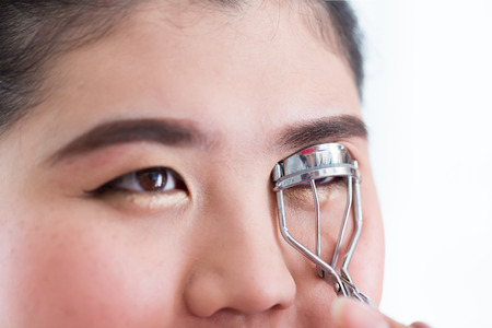 curler: makeup artist using eyelash curler on woman face