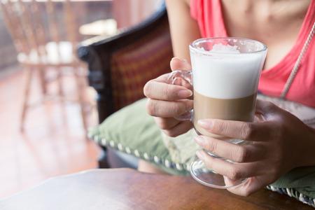 mujer tomando cafe: Mujer beber un café caliente en el café