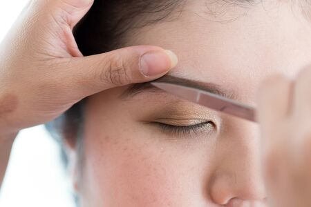 pretty woman face: makeup artist used eyebrow scissors makeup a pretty woman face Stock Photo