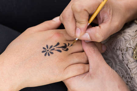 body paint: body paint, artist used paintbrush drawing art on hand person Stock Photo