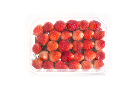 red ripe strawberry in plastic box of packaging for sale, isolated on white background Stock Photo