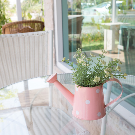 flower arrangements: flowers vase decorated on mirror table at living room, artificial flowers in vase watering can