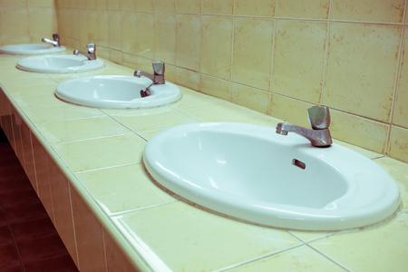 piastrelle bagno: lavandino lavare bianco in bagno con il vecchio rubinetto d'argento