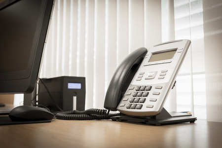 telephone handset: telephone and computer on table work of room service office Stock Photo