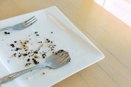 leftover: leftover of cake with fork and spoon on white plate