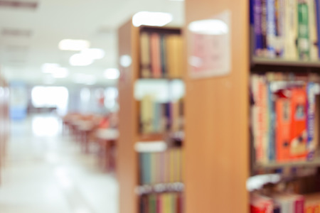 library with table desk and bookshelf, abstract blur defocused background Foto de archivo
