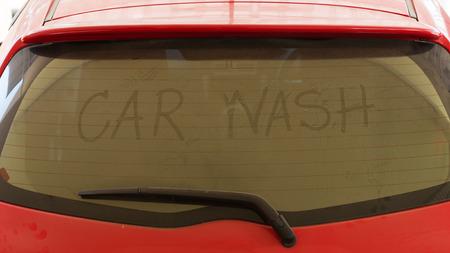dirty car: text of car wash on back mirror dirty car