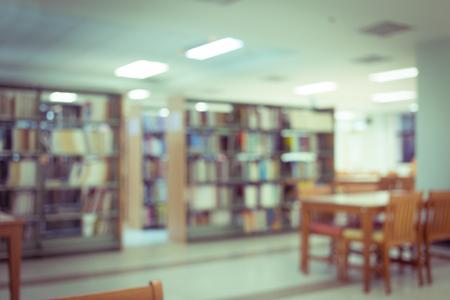 edificio escuela: estantería y mesa de escritorio en la biblioteca, educación blur fondo desenfocado Foto de archivo