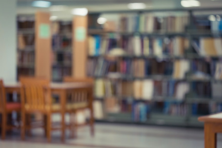 school desk: bookshelf and table desk in library, education abstract blur defocused background Stock Photo