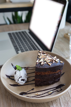 notebook computer: cake chocolate on wood table work with laptop notebook computer