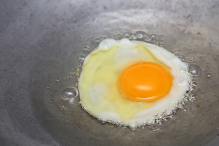 cooking oil: cooking fried egg in hot pan with oil