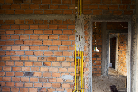 shrouded: brick wall in residential house building construction site with cable wires shrouded hard pipe tube plastic