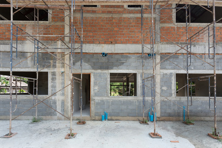 housebuilding: building residential construction house with scaffold steel for construction worker, wall made from brick