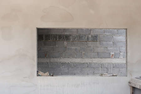 housebuilding: window on cement wall with brick wall background in construction building Stock Photo