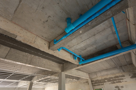 housebuilding: water pipes pvc plumbing under cement ceiling of second floor in construction site building