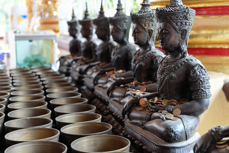 chiang mai: Angel statue and monks alms bowl with put the coins by donors in Wat Suan Dok temple, chiang mai, thailand