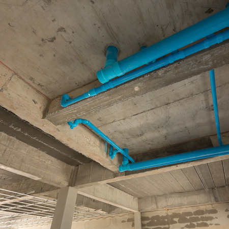 second floor: water pipes pvc plumbing under cement ceiling of second floor in construction site building