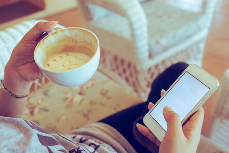 shopping online: woman drinking hot coffee in cafe and use a mobile phone with blank touch screen, playing social network and shopping online on app smartphone