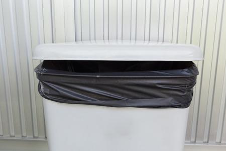 trashcan: black bag plastic in white trashcan bin