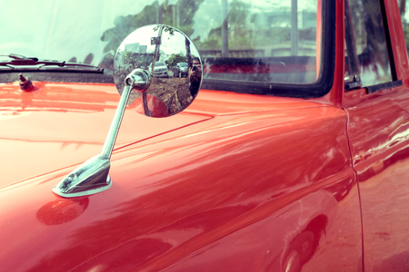 sideview: close-up mirror sideview of colourful classic car, image used filter vintage