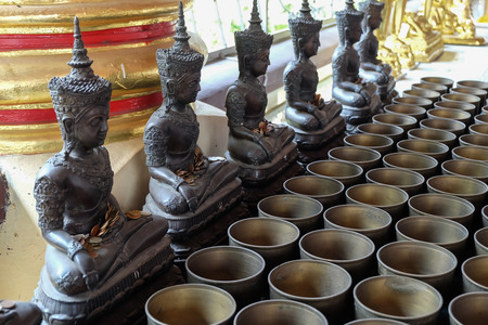 chiangmai province: Angel statue and monks alms bowl with put the coins by donors in Wat Suan Dok temple, chiang mai, thailand
