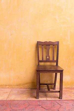 silla de madera: asiento de la silla de madera y cemento de naranja fondo de la pared de mortero Foto de archivo