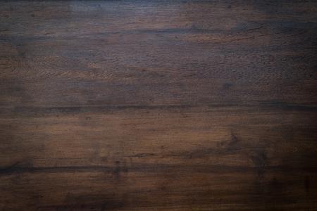 morenas: madera de la textura del grano marrón, fondo de pared de madera oscura, vista desde arriba de la mesa de madera