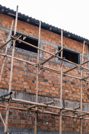 housebuilding: building residential construction house with scaffold for construction worker Stock Photo