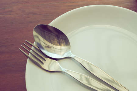 dishware set on wood table with plate, spoon and fork, image used filter vintage Stock Photo