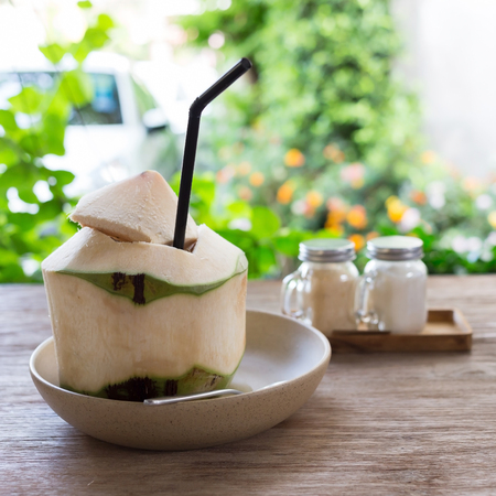 coconut palm: fresh coconut water drink on wooden table with natural blur background