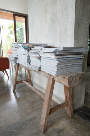 magazine stack: stack of magazine book on wooden table shelf in living room with sofa furniture