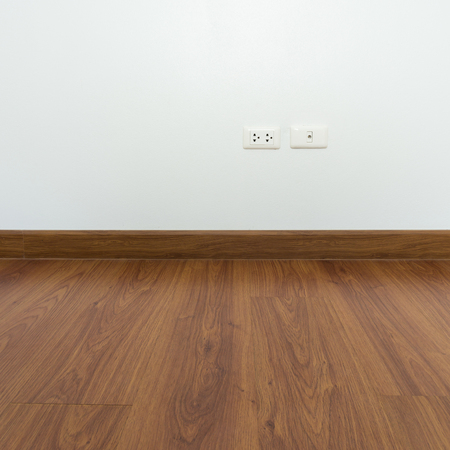 white wood floor: empty room with brown wood laminate floor and white mortar wall background