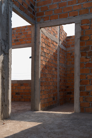 housebuilding: wall made brick in residential building construction site with dirty cement floor