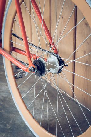 dientes sucios: bicicleta fija del engranaje estacionado con la pared de madera, de cerca parte de la imagen de la bicicleta